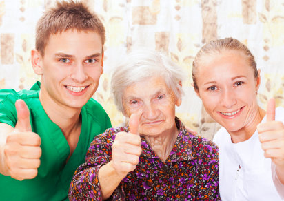 elderly woman with two caretakers showing thumbs up